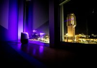 An Alexa home device sits on a darkened window ledge, bathed in purple laser light coming from a tower in the BG.