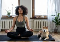 Young african american woman in apartment meditating, dog next to her.