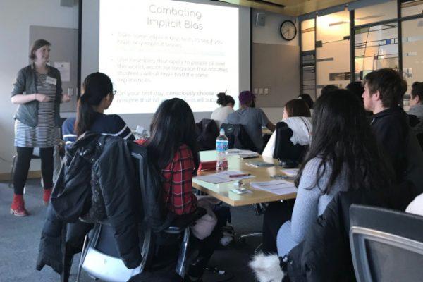 Women instructing class, on screen: Combating Implicit Bias
