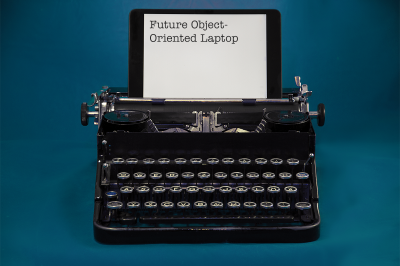 """A typewriter with an iPad propped up where the paper usually goes. The iPad reads """"Future Object-Oriented Laptop"""""""