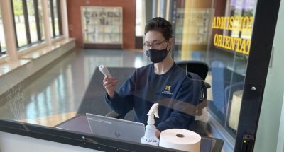 A masked student worker sits behind a screen. They are holding a thermometer and are sitting in front of a laptop.