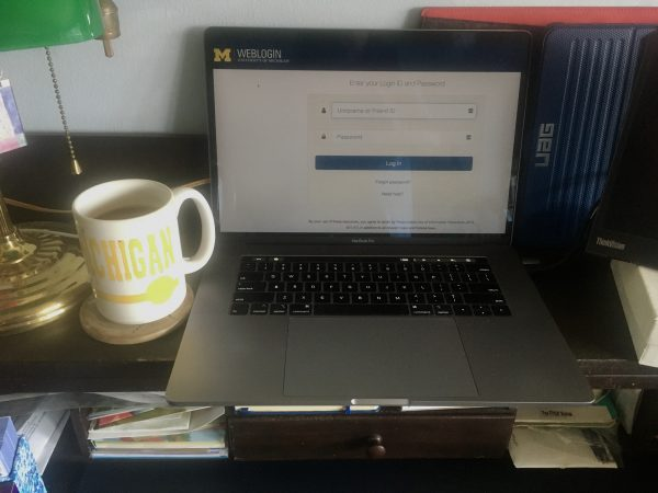 Image of a Mac laptop showing the weblogin window sitting a home desk next to U-M coffee cup.