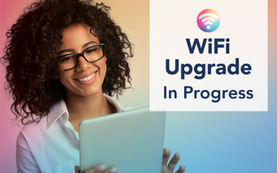 A Black woman in a white shirt wearing glasses is smiling while using her tablet. Text says WiFi Upgrade In Progress