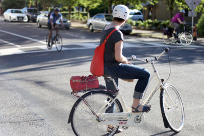 A bicyclist pauses at an intersection to let another bicyclist pass by.